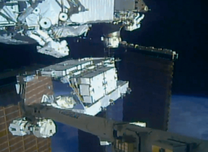 Solar panels on the International Space Station, with two astronauts in white boxy suits clinging to the side of the structure, while Earth sits in the background.
