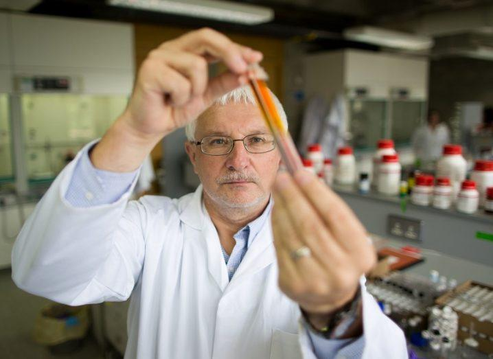 Prof Michael Zaworotko in a white coat in his lab holding up the material.
