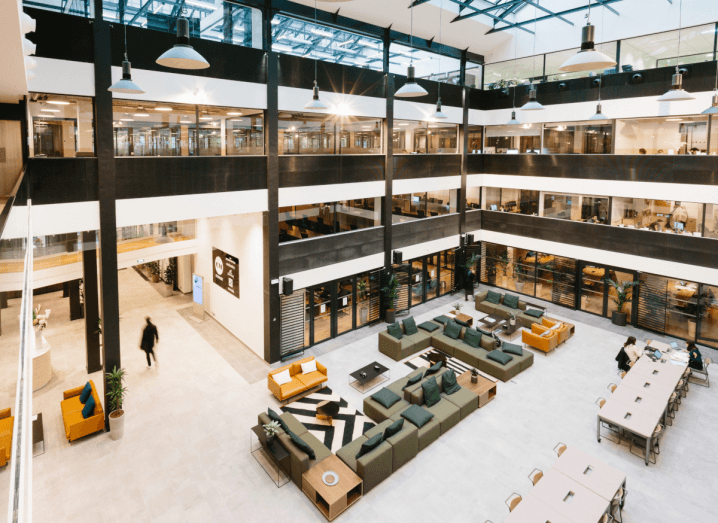 A photograph of a large common space in a WeWork building, taken from the third or fourth floor. The view below is of numerous sofas and long desks with many chairs lined up along them. The room is bright and modern, with black paint framing the windows overlooking the common area. Each of these windows contains a meeting room or other sort of office space.