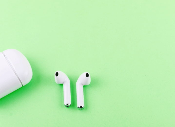 AirPods and a charging case on a lime green background.