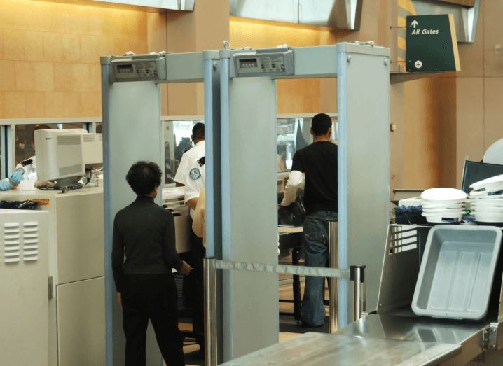 A woman in a grey polar neck jumper and black trousers walks through a metal detector at airport security. There are trays for passenger belongings to the right of the metal detector and to the left of it, there are airport security agents wearing blue rubber gloves. Beyond the metal detector, there is a sign on a brown wall that directors passengers to all departure gates.