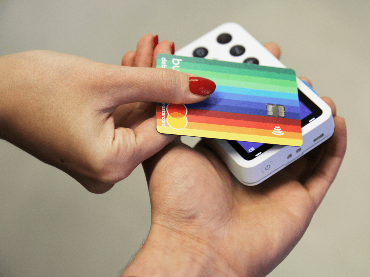 A hand with red nail polish holding a rainbow-designed Bunq card taps the card against a Contactless reader that is held by another person.