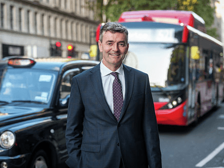 A man in a black suit and burgundy tie with grey hair smiles into the camera while standing on a London street in front of a black cab and a red bus.