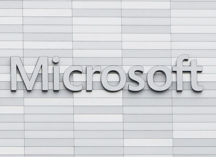View of Microsoft logo on white-grey building façade.