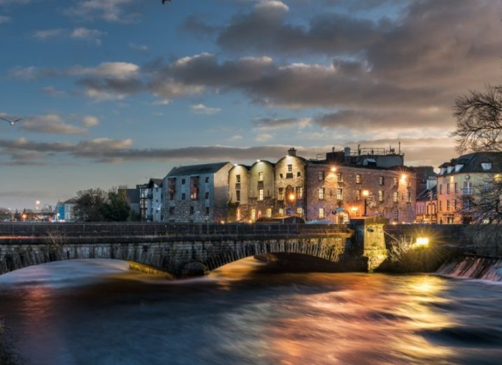 Sunset over Galway's Bridge Mills, with light reflecting on a river.