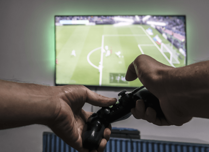 Two hands holding a PlayStation 4 controller in front of a large TV screen that is mounted on a wall over a radiator. The game on the TV screen is Pro Evolution Soccer.