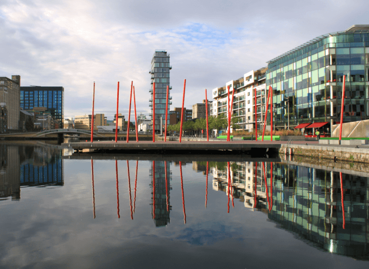 The skyline of Dublin's Grand Canal Dock, taken from the north side of the body of water. The view includes apartment blocks and office buildings as well as an art installation with red poles sticking out of the ground.