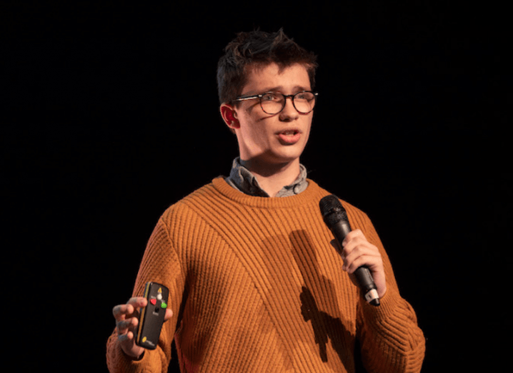 A young man in an orange jumper and thick-rimmed glasses stands on a stage, speaking into a microphone.