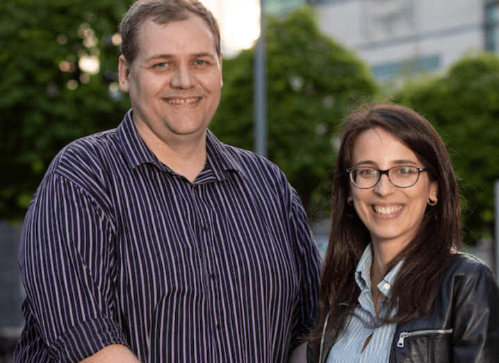 The two founders of P-Sense stand outside in a city in front of trees. One is a tall man wearing a striped shirt, the other is a woman with dark hair and glasses.