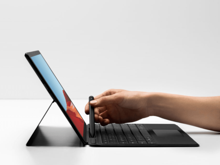 A propped up Surface tablet, and a user picking up a stylus that is built into the keypad of the device and can be removed.