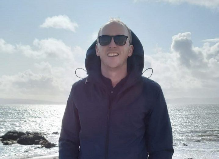 Dr Enda Barrett wearing a dark jacket and sunglasses while smiling against backdrop of sunny sky and ocean.