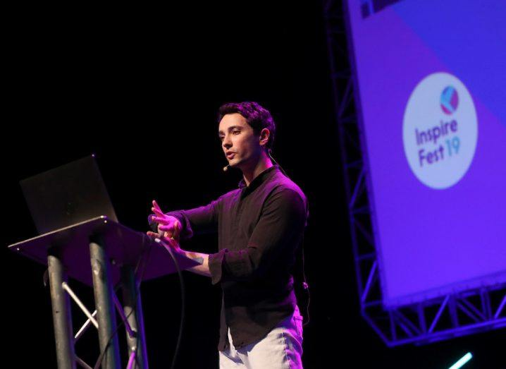 A man in a black shirt stands on stage in front of a screen that reads, Inspirefest 2019.