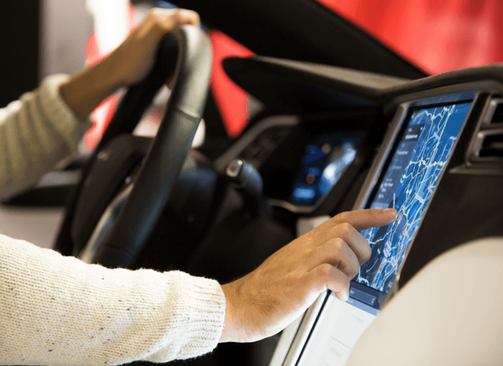 A person in a beige knitted jumper sitting behind the steering wheel of a Tesla, touching the computer built into the car's console.