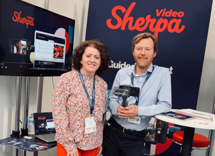 A woman in a floral blouse stands in front of a large TV that has the Video Sherpa logo displayed on it. The woman has curly brown hair and she is smiling. To her right, there is a man with light brown hair and a beard. He is wearing a blue shirt.