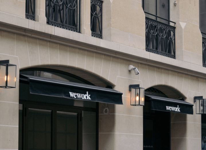 The facade of a beige building with shutters that say 'WeWork' on them.
