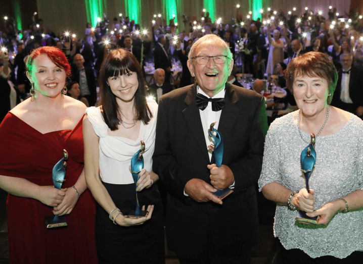 A woman with dyed red hair holds an award while wearing a red dress, beside a woman with black hair and a full fringe who is wearing a white top and black skirt. Beside her is a man in a tuxedo, also holding an award, and a woman to his right who is wearing a silver top and black skirt.