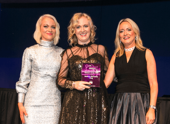 A woman in a silver dress standing beside two women in black dresses. All three women have blonde hair. The woman in the middle is holding a purple award.