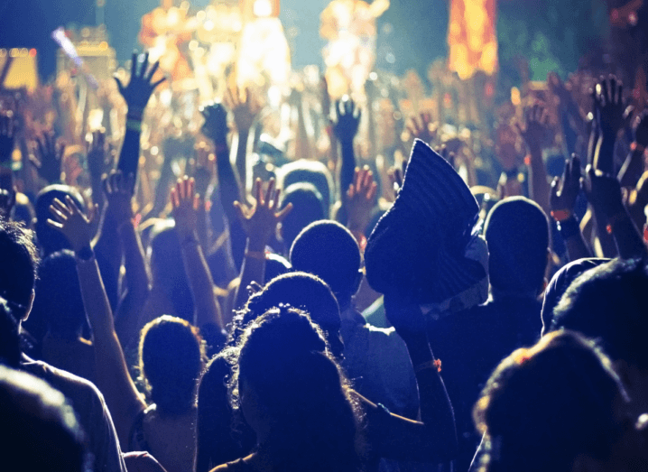 A crowd of fans in the audience at a show, with their hands in the air.