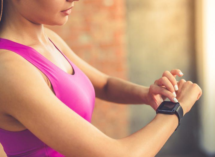 View of woman in pink sports bra holding up wrist and tapping on her Fitbit.