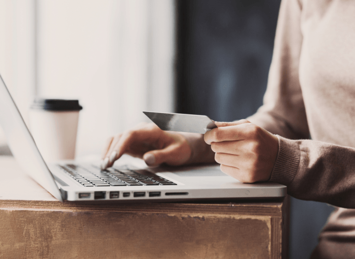 A person typing on a MacBook with one hand and holding a payment card in the other hand. They have a coffee on the the table beside them in a disposable cup. They are wearing a beige jumper and grey nail polish.
