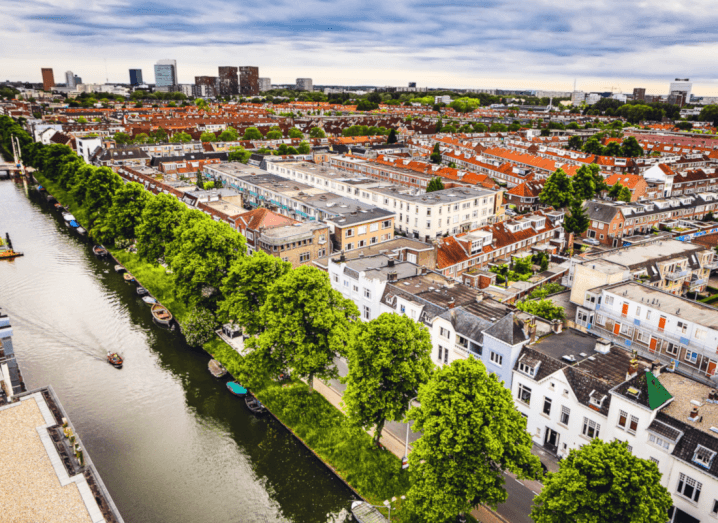 A view from above the city of Utrecht. A canal lined by trees is visible in front of rows and rows of traditional Dutch-style buildings.