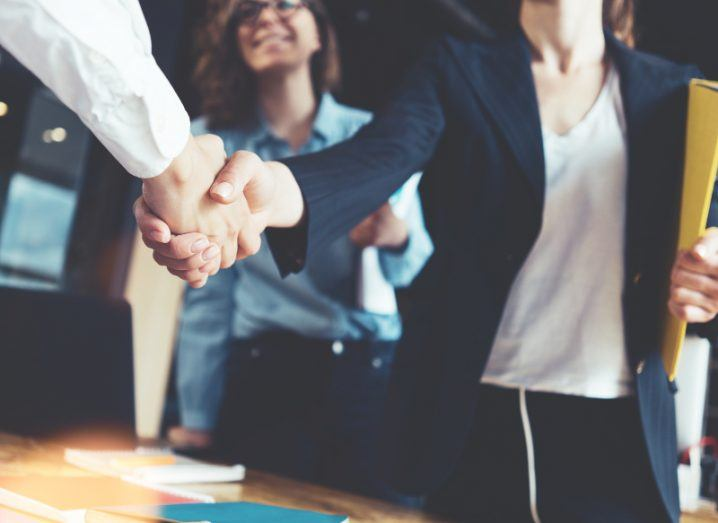 A business man reaches out the hand of a businesswoman across a desk. She is standing beside her business partner who is smiling, having just secured a deal.