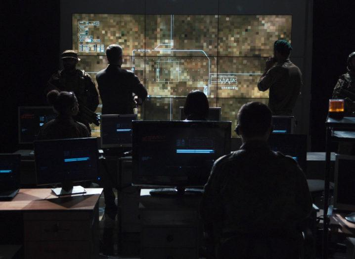 View of people in a darkly lit war room peering at a screen anticipating cyberattacks.