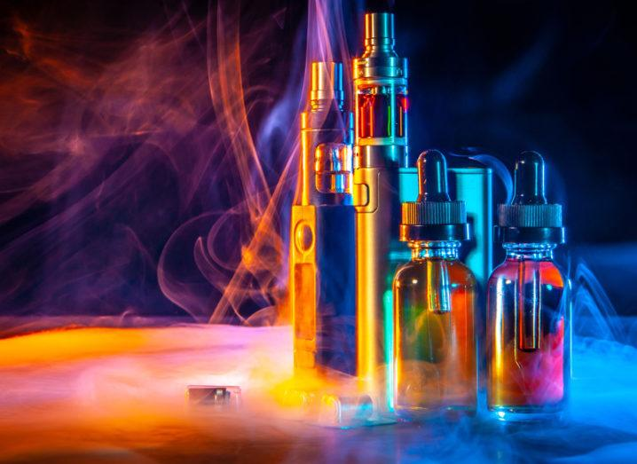 View of vaping paraphernalia and e-cigarettes with liquid against rainbow lights and fog.