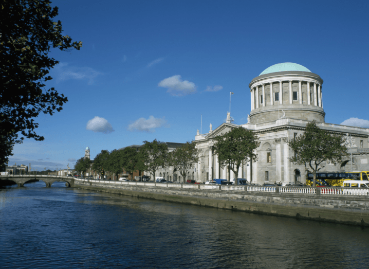 A large white courthouse with a green domed roof sits in front of Dublin's Liffey river on a sunny day.