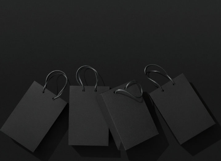 View of black shopping bags lying flat against darker black background.