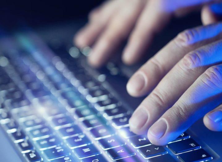 View of fingers floating over a blue backlit keyboard.