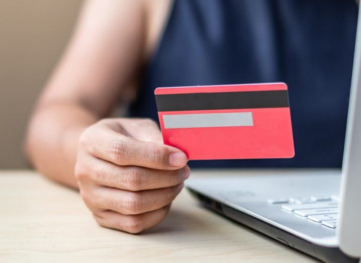 A woman's hand holding a credit card as she inputs the data on a laptop to complete an online transaction.