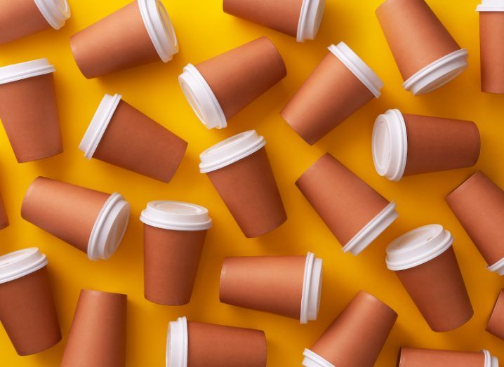 Scattered brown disposable coffee cups with white plastic lids on a burnt orange background.