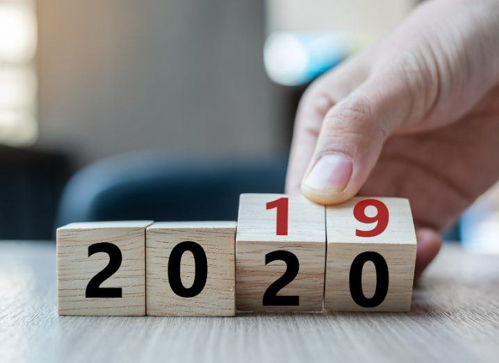 A hand reaches down to a row of four wooden cubes that read '2019', turning the last two cubes to read '2020' instead.