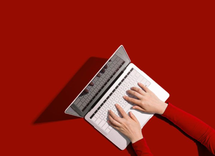 View from above of person in red sweater using silver laptop with hands on keyboard against red background.