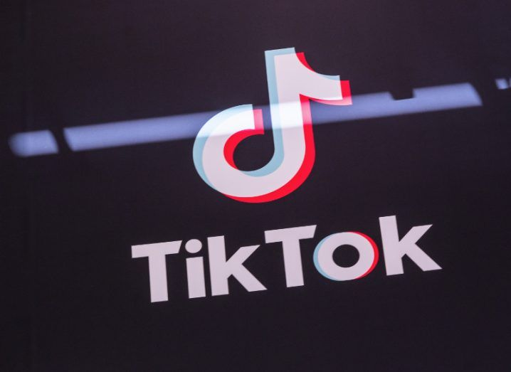 View of white and pink TikTok logo with music note on black background.