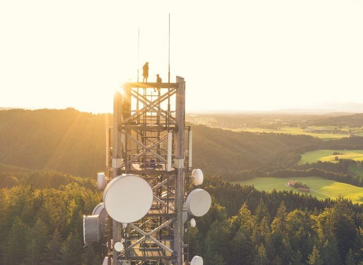 The top of a telecoms tower with satellite dishes on it, against the background of a sunset and rolling green hills.