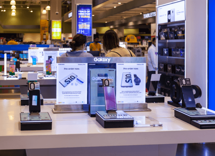 Different models of the Samsung Galaxy S10 on display at an event or convention. People are walking around in the background beyond the phones.
