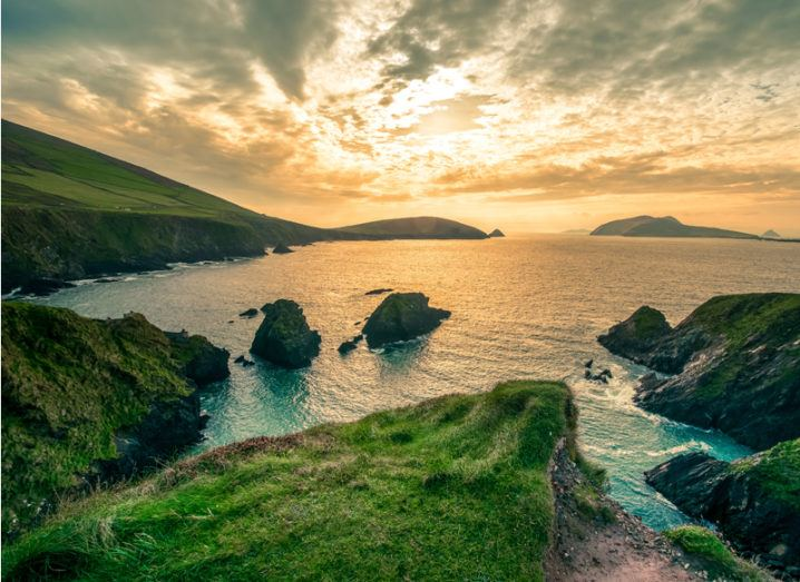 The cliff face of the Dingle Peninsula reaching out into the Atlantic Ocean as the sun rises in a cloudy sky.