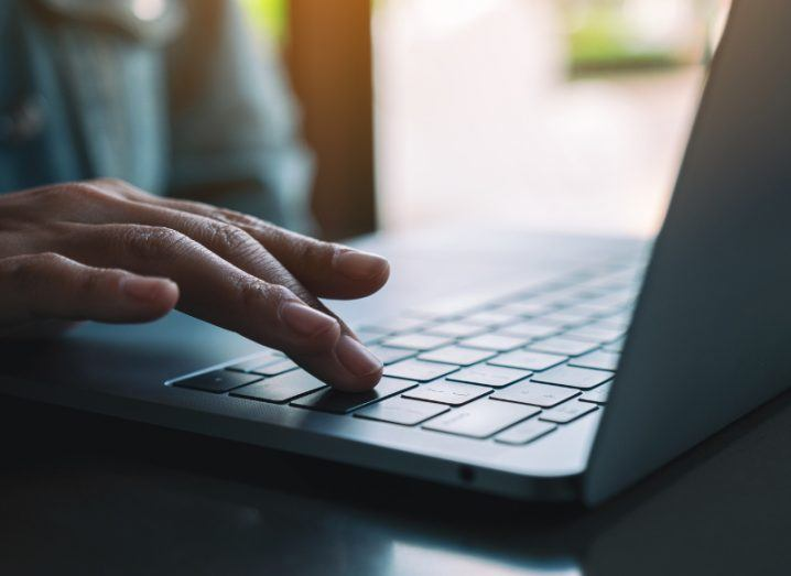 Closeup image of a hand typing and pressing finger on laptop computer keyboard.