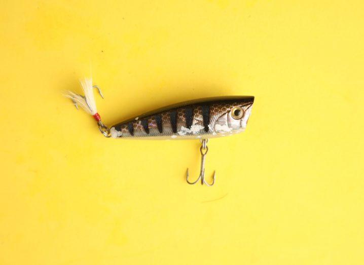A mock fish fishing lure with three-pronged hooks dangling from its belly and its tail.