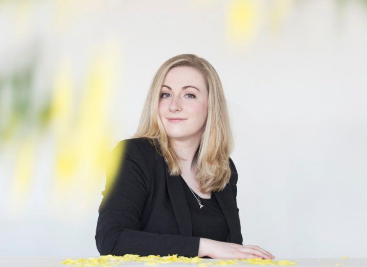 A blonde-haired woman wearing a black suit leans on a table with one arm. She is in a white room.
