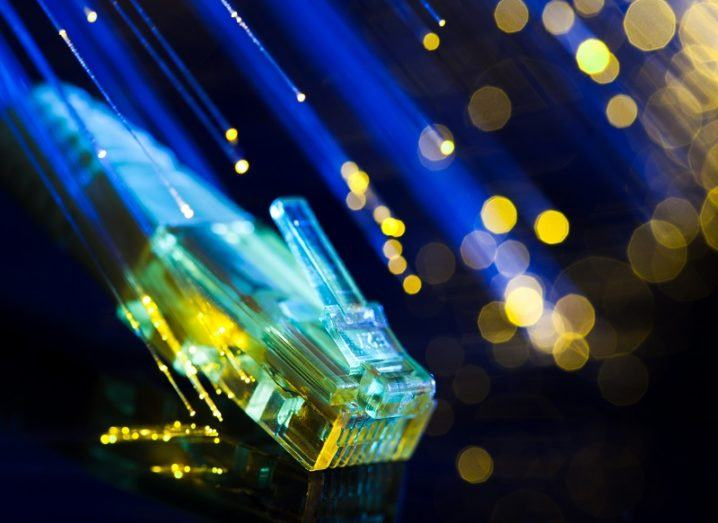 Ethernet cable lit up by surrounding blue and yellow fibre-optic cable.