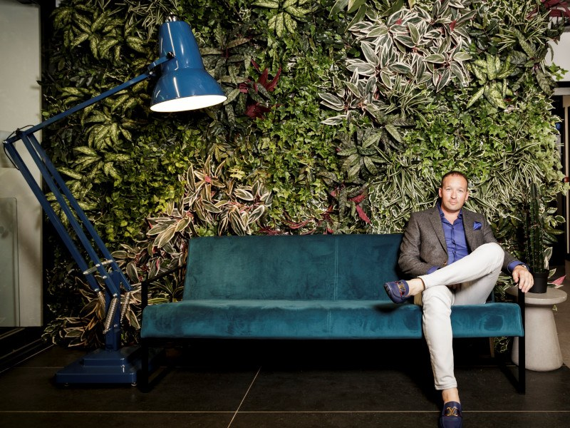 A man in a casual suit sits on a green couch against a floral wall.