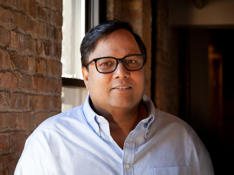 View of man with dark hair and glasses in light-coloured shirt smiling while sitting in front of an exposed-brick wall.