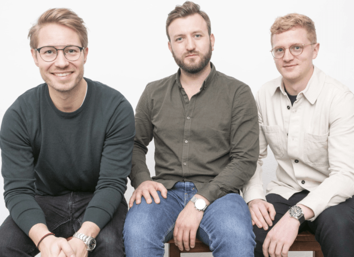 Three men sit in a row against a white background.
