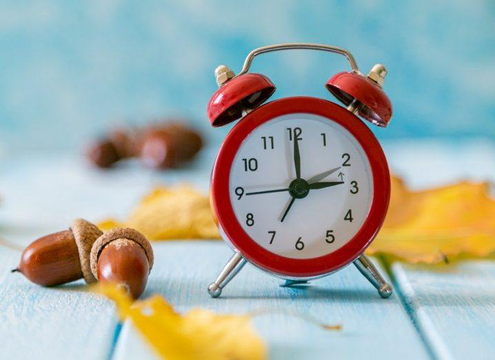 Small, red alarm clock on blue wooden decking surrounded by autumnal leaves and acorns.