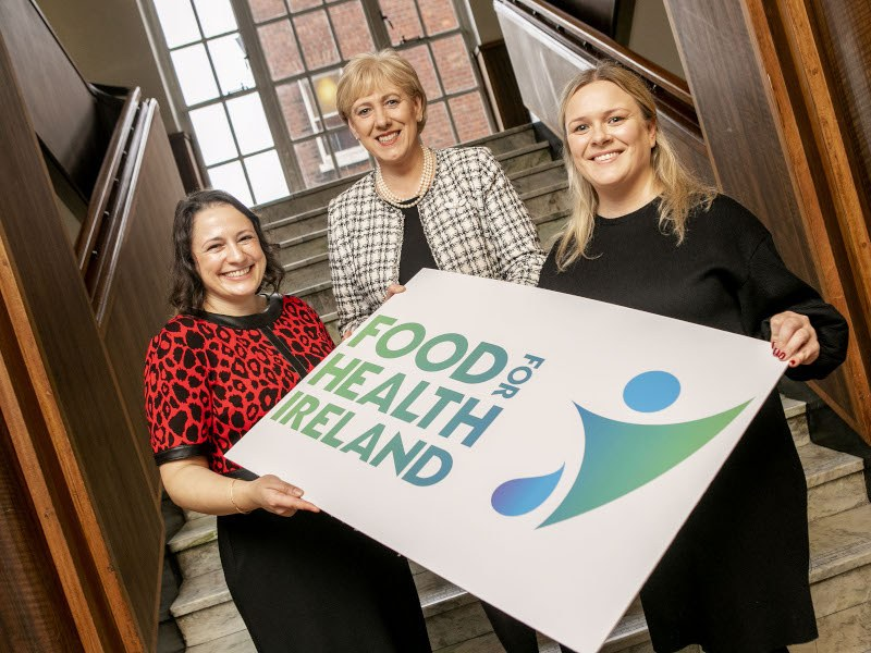 Three women stand on a staircase holding a sign that reads 'Food for Health Ireland'.
