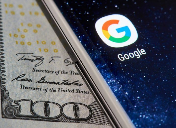 A phone sitting on a $100 bill with the Google app logo on-screen.