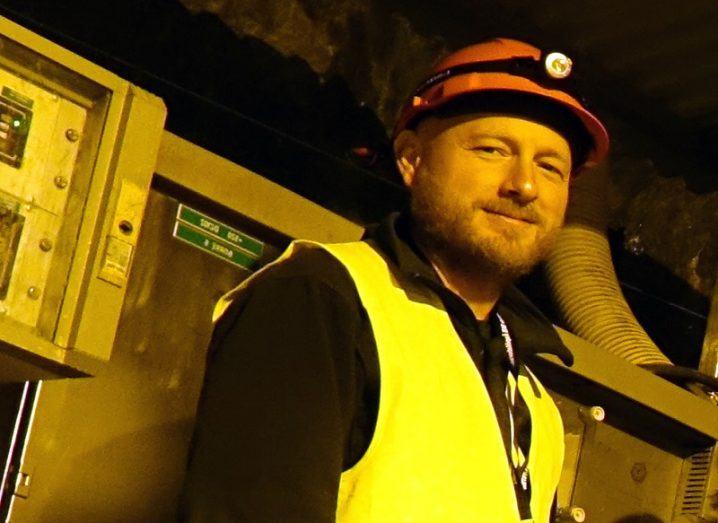 Henrik Drake in a hardhat and hi-vis jacket underground beside industrial machinery.